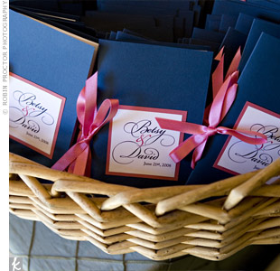 Pink accents on navy card stock set the tone for the wedding's stationery. The programs' design first appeared on the invitations.