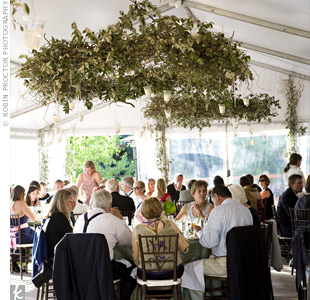 To bring the outdoors in, the coordinator created three chandeliers out of curly willow and incorporated twinkle lights and votive candles. Tall curly willow bundles spruced up the tent's perimeter.