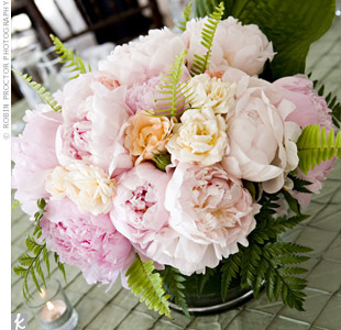 Glass cylinders were lined with ti leaves and filled with peonies, ranunculus, garden roses and ferns. Large chunky votives lit each table as the sun set.
