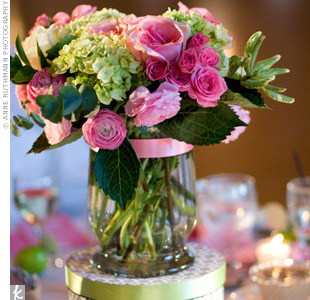Damask-print hat boxes evoked a vintage, romantic feel and gave height to the pinspotted arrangements of pink roses and green hydrangeas.
