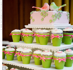 Shannon and Kayu's pink wedding cake was decorated with green sugar flowers and topped with a pair of birds. Below, cupcakes in green flower pots kept with the garden theme.