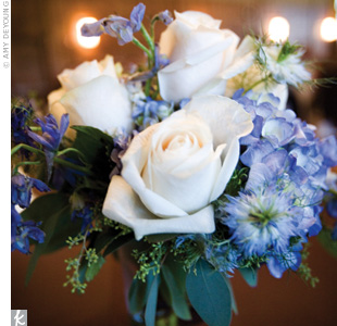 The reception tables were decorated with low centerpieces of white roses and blue hydrangeas and nigellas to incorporate the wedding's color scheme.