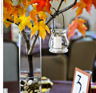 Mara made the centerpieces too. She filled tall, square vases halfway with river rocks and placed real branches of fall leaves in all of them.