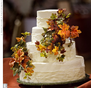 As a rustic alternative to ribbon, raffia was wrapped around the bottom of each cake tier. Colorful fall leaves brightened up the white buttercream-frosted dessert.