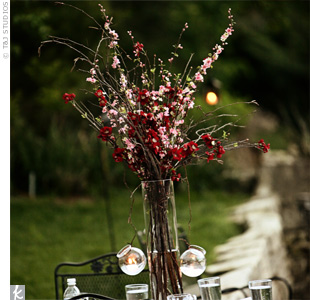 Pink silk cherry blossom branches stood in tall cylindrical vases, while glass globes containing votive candles hung from the sides of each arrangement.