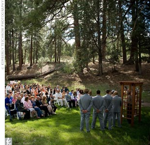 Asheley and Nate's ceremony took place outside on the Aspen Hall grounds. The couple borrowed a wooden arch to use as their arbor and set up simple white chairs for their guests. Because it had rained the entire week before the wedding, the trees and grass were especially lush.