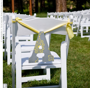 "Asheley got the idea to monogram the ceremony chairs from the DIY area on TheKnot.com. She went to her local craft store and picked up two wooden initials -- an ""A"" and an ""N"" -- and painted them green and yellow. She hung the initials with yellow ribbon on the ceremony chairs to designate the bride's side from the groom's."