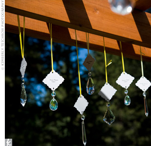 Asheley and Nate decorated their wooden arch with hanging crystals they purchased online. Pearlized card stock printed with guests' names was attached to each crystal so that they doubled as escort cards.
