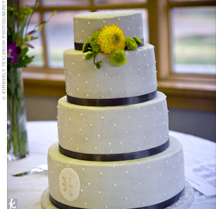 Asheley and Nate wanted a sleek and modern cake. To get the look, their baker created a shorter top layer and frosted the cake with light-gray buttercream. White dots, fresh yellow flowers, and the couple's monogram finished it off. The cake was filled with three flavors: spice cake with caramel apple filling, white cake and Bavarian cream, and cho ...