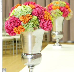 Urns filled with orange roses and green and pink hydrangeas rested on the stage where the couple exchanged self-written vows.