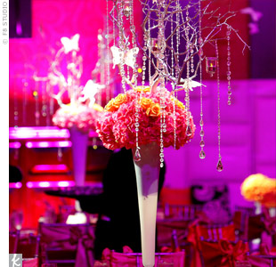 Different arrangements decorated the 45 tables, including clay vases of branches with butterflies and crystals dangling over hydrangeas and roses, as well as cylinders of submerged flowers topped with white feathers.