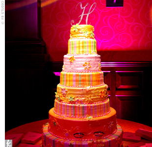 "A silver ""H"" for the couple's last name topped the eight tiers of red velvet, white chocolate and strawberry cheesecake covered in fondant in the same shades as the bouquets."