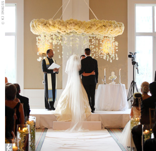 Both a priest (for Kerrie's religion) and a rabbi (honoring Cory's faith) officiated. The couple incorporated Jewish and Catholic traditions, like marrying under a huppah and lighting a unity candle.