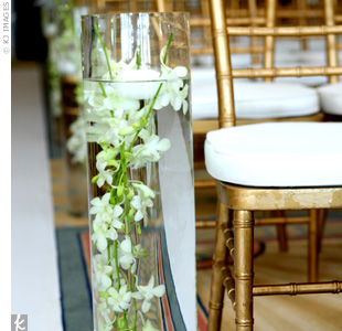 Ten cylinder vases with submerged orchids and floating candles lined the aisle and were lit up to add a romantic glow to the indoor space.