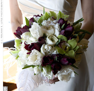 An elegant mix of tulips, ranunculus and cymbidium orchids was accented by a single ostrich feather to match the centerpieces.