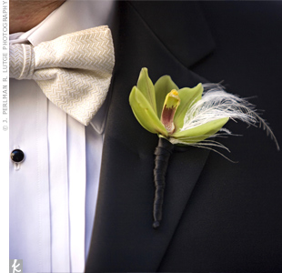The groom wore a single cymbidium orchid paired with a small ostrich feather that coordinated with the larger one in the bridal bouquet.