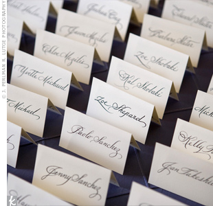 To tie in with the turn-of-the-century theme, the escort card display was designed in the formal style of that era. Guest names were handwritten in calligraphy and the cards sat atop plum pintuck linens.