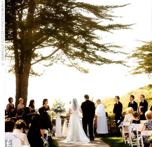 The couple exchanged vows on a grassy cliff overlooking the beach. Since the scenery was so beautiful by itself, the couple only added clusters of hydrangeas, irises, and calla lilies along the aisle.