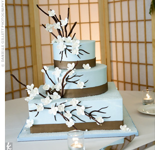 A square bottom layer was topped with two round tiers, all of which were frosted with sky-blue buttercream. The finishing touches: cherry blossom branches with petals made of spun sugar.