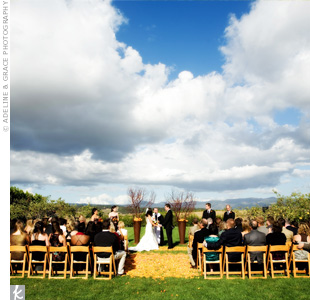 The couple exchanged vows in the late afternoon in an apple orchard overlooking the Carneros Valley. A petal-strewn aisle added some fall colors to the setting.