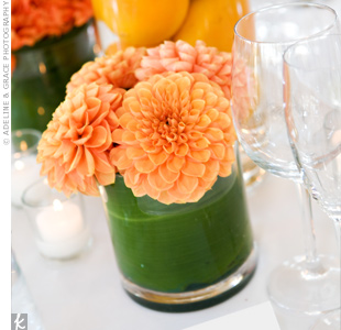 Small clusters of orange dahlias punched up the all-white table linens. Leaves were wrapped around the inside of the vase to add even more color.