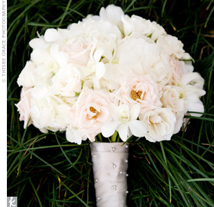 Roses, peonies and orchids combined for a soft bouquet with classic style. Pearl-topped pins accented the ribbon that wrapped around the stems.
