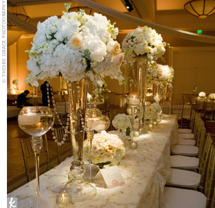 Arrangements of roses, stock and hydrangeas topped both round and rectangular tables. Candlelight bounced off the vases and crystals hanging from the taller centerpieces.