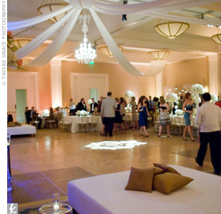 "Draped silk softened the ballroom and created a focal point on the dance floor, where gobo lights flashed the couple's monogram. Lounge-style ""beds"" added a modern vibe to the formal décor."