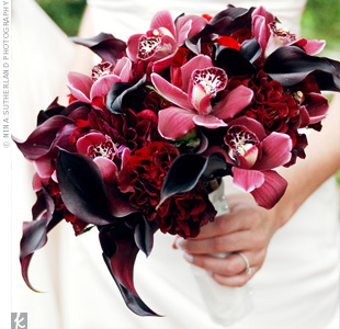 A lush, textured mix of Black Magic roses, plum calla lilies, deep-red peonies and ranunculus provided a darker background that made the brighter cymbidium orchids stand out.
