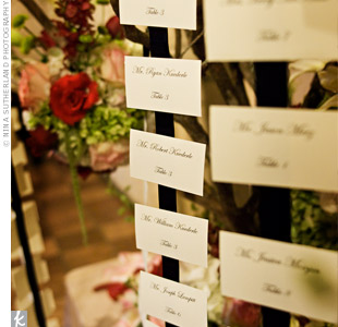 Guests found their names and table numbers stylishly displayed on ribbon that was hung from the branches of the table display. Coordinating flowers added a pop of color.