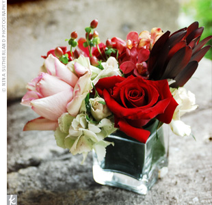 Square vases in varying heights were filled with mini calla lilies, roses, orchids, safari sunset, lotus pods and cymbidium orchids in the couple's wedding colors.