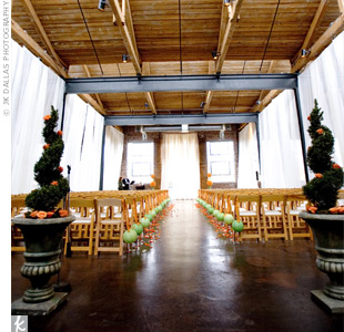 The ceremony and reception were held in the same space, but a set of sheer white drapes separated them effortlessly. Two live evergreen topiaries framed the aisles with orange ribbons trailing down either side. A green paper lantern, attached to tangerine-and-lime striped ribbon, hung from each chair along the aisle.