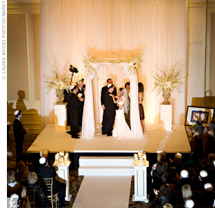 Emily and Neil exchanged vows under a huppah in a traditional Jewish ceremony. The flat top of the arch was covered with a lace and linen tablecloth that belonged to Emily's grandmother. White fabric lined the aisle along with six cream-colored, gold-leaf pedestals filled with hurricanes of pillar and votive candles.