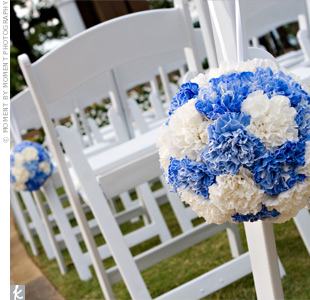 Blue-and-white carnation pomanders, attached to the chairs with ribbon, swung in the breeze.