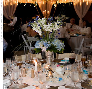 The combination of tall bear grass and cream stock shooting out of silver urns, accented with shorter bunches of cream and blue hydrangeas, made for very dramatic centerpieces. Cream and powder blue rose petals scattered beneath the arrangements gave the tables a fresh, romantic feel.