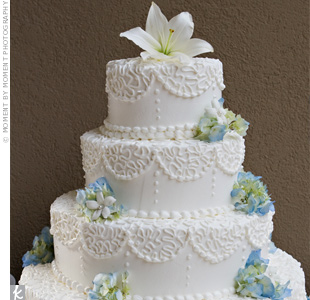 A buttercream scroll design draped over the four tiers of cake, while white Swiss dots trickled down the sides. A large white lily served as the topper and sprigs of blue hydrangeas and stephanotis rested on each tier.