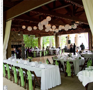 Katie and John designed their outdoor wedding around simple elegance and a black, white, and apple green color scheme. Festive lanterns and floor-to-ceiling curtains hung down for a cozy but fun feel. Bright green chair ties accented the crisp white linens, tying the whole look together.
