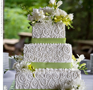 White-on-white swirls gave the three-tiered cake lots of texture, while apple-green ribbons and little clusters of fresh flowers brought in the rest of the color palette.