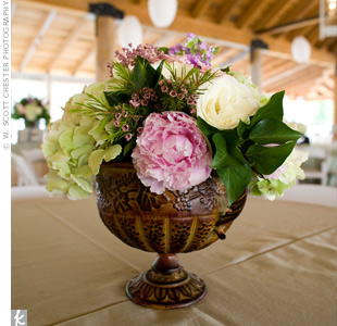 The table arrangements followed the soft pink, green, and lavender color palette with full peonies, roses and hydrangeas in antique-style urns.
