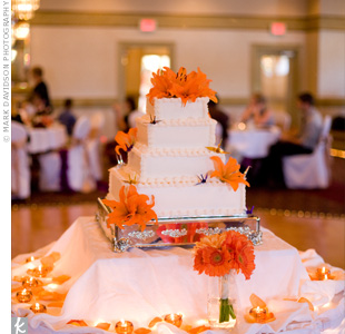 The four-tiered wedding cake was frosted with ivory buttercream and decorated with orange Asiatic lilies and paper cranes. Scattered at the base, orange petals and tea lights highlighted the dessert.