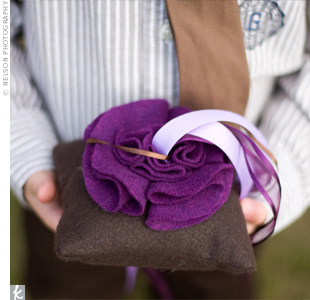 Violet ribbons kept the couple's rings tied to a gray pillow decorated with a fabric rose.