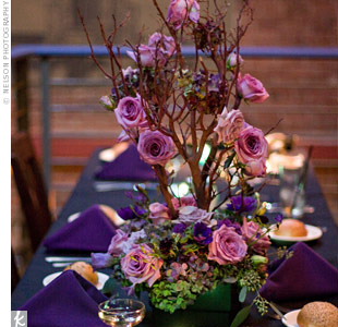 Alternating arrangements of iron birdcages filled with roses, hydrangeas, and votives, and tall branches adorned with the same blooms, topped the rectangular tables.