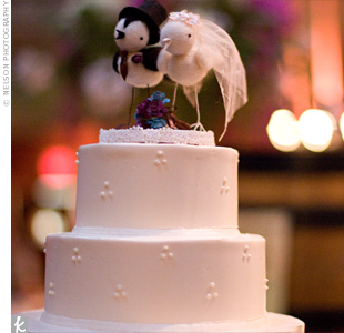 "Funky, handmade birds (the ""groom"" bird even had a top hat!) added a touch of quirkiness to the four-tiered buttercream cake with Swiss dots."