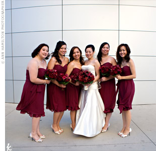 The dark-red, knee-length dress that each of the bridesmaids wore had a sweetheart neckline, a shirred bodice and a ruffled hem. Pearl necklaces and bracelets paired well with the elegant dresses.