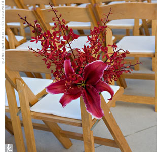 Oriental lilies and orchids in the signature hue adorned the chairs on the aisle. The Asian-inspired design complemented the garden setting.