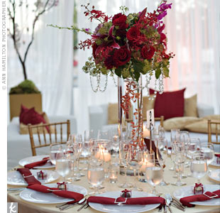Tall vases with submerged orchids held lush hydrangeas, Oriental lilies, orchids and roses. Crystals draped around the edges played off the sparkle of the napkin holders.