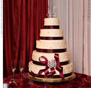 Ruby-red ribbon on the five-tiered cake brought in the day's signature color, and a metallic topper and a brooch worked in extra sparkle.