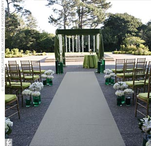 Clusters of flowers, like lilies, roses, and orchids, filled vases of dyed water along the aisle. The canopy and seat cushions matched the green scene