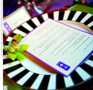 Menu cards and a small gem coordinated with the escort cards and rested on top of modern, black-and-white dinner plates. Green napkins and cymbidium orchids brought in the other color of the palette.