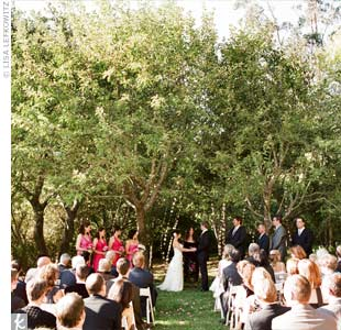 The couple didn't need an arbor; the trees in their reception site's backyard beautifully framed the spot where they exchanged vows.